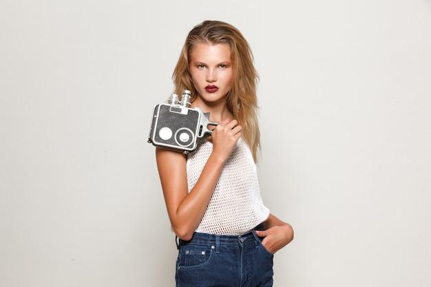 Frontales porträt einer mädchenblondine, die in weißer modekleidung posiert, in die kamera schaut und eine retro-kamera in der hand hält.