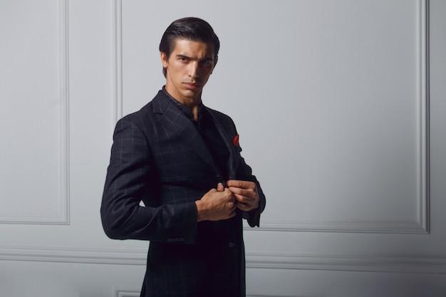 Frontalporträt des selbstbewussten jungen mannes im schwarzen anzug mit rotem seidenschal in der tasche, über weißem hintergrund. speicherplatz kopieren.