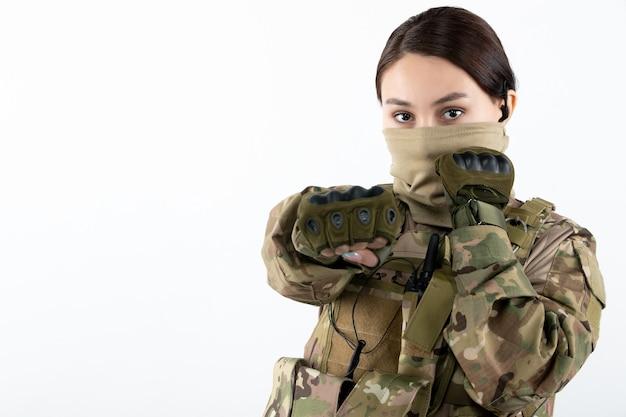 Frontansicht der soldatin in militäruniform auf weißer wand