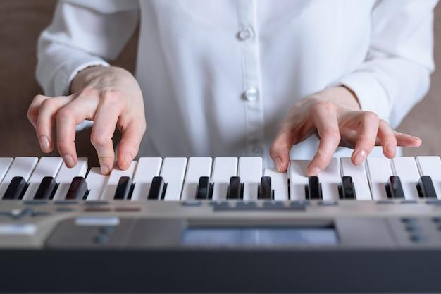 Frontansicht der weiblichen hände geübt, den synthesizer spielend