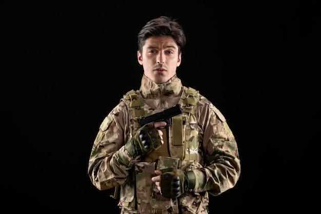 Frontansicht des militärs in uniform mit pistole an schwarzer wand