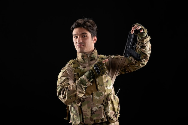 Frontansicht des militärs in uniform mit schwarzer pistolenwand