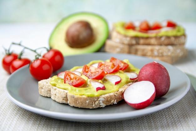 Frontansicht des toasts mit avocado, tomate und rettich und den bestandteilen auf einer platte
