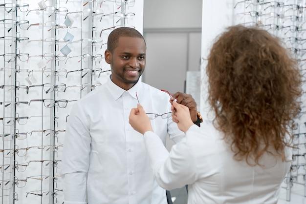 Frontview des lächelnden mannes versuchend auf brillen im optischen shop.