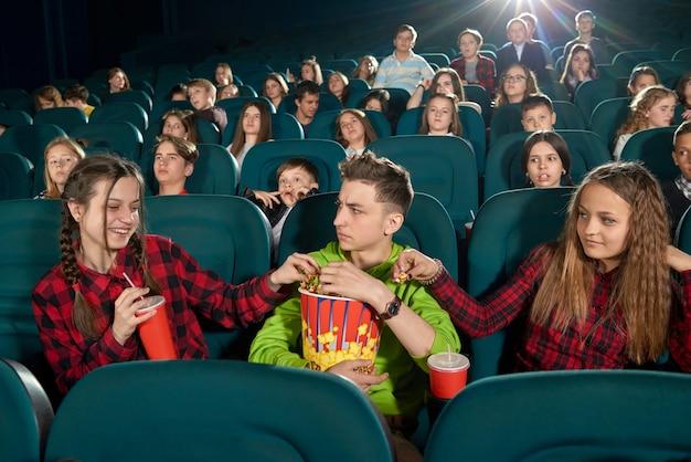Frontview von drei freunden, die popcorn essen, indem sie film anschauen.