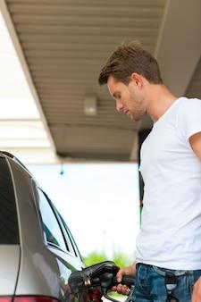 Froschperspektive des mannes auto an der tankstelle betankend