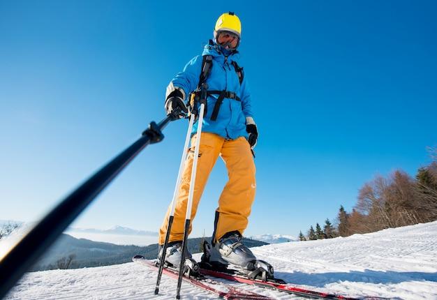 Froschperspektive eines männlichen skifahrers, der ein selfie unter verwendung des selfie stockes aufwirft auf eine steigung am winterurlaubsort in den bergen nimmt.