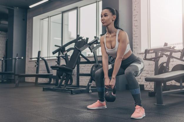 Froschperspektive eines sexy weiblichen athleten, der mit kettlebell an der turnhalle trainiert