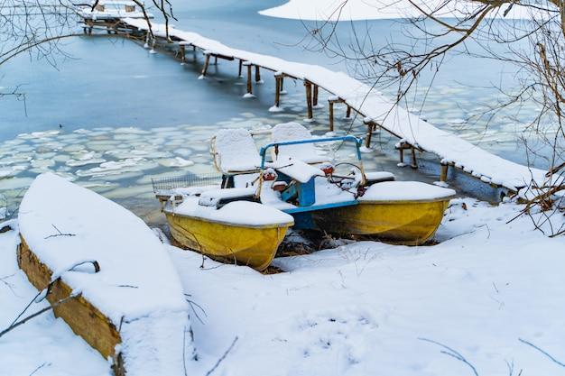 Frosen fluss und ein katamaran, die auf dem flussufer bedeckt mit schnee nahe der langen holzbrücke stehen.