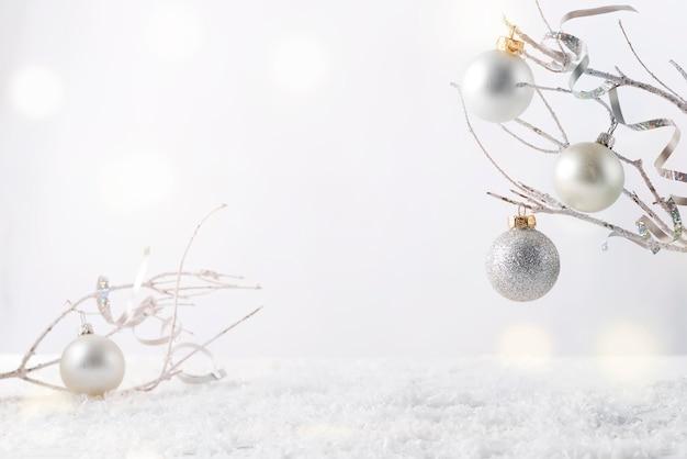 Frostiger ast mit schnee und weihnachtsdekoration ich auf weiß. bringen sie ihr produkt an