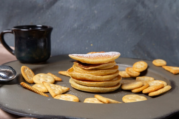 Frotn ansicht pfannkuchen und cracker mit tasse milch auf dem grauen hintergrund frühstück essen mahlzeit süß