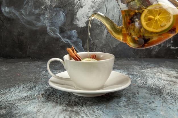 Frotn view kessel mit tee, der in die tasse am morgen der teezeremonie der dunklen oberfläche gießt