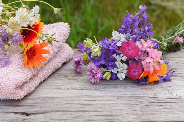 Frotteehandtuch für badverfahren mit thymianblüten auf den holzbrettern in natürlichem hintergrund. spa-produkte und zubehör.