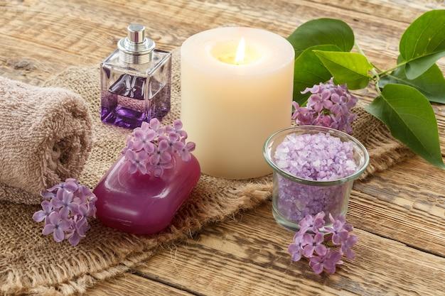 Frotteehandtuch, meersalz für badezimmerverfahren, brennende kerze, seife, eine flasche parfüm und lila blumen auf sackleinen und alten holzbrettern. spa-produkte und zubehör.