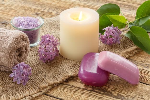 Frotteehandtuch, seife für badezimmerverfahren, meersalz, brennende kerze und lila blumen auf sackleinen und alten holzbrettern. spa-produkte und zubehör.