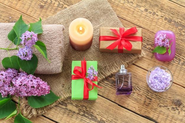 Frotteehandtuch, seife und meersalz für badezimmerverfahren, eine brennende kerze, geschenkboxen, eine flasche parfüm und lila blumen auf sackleinen und alten holzbrettern. ansicht von oben. spa-produkte und zubehör.