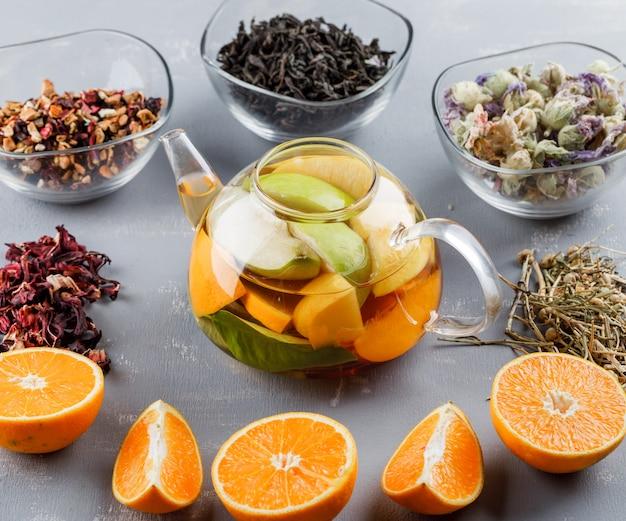 Frucht aufgegossenes wasser in einer teekanne mit kräutern, orangen-hochwinkelansicht auf einer gipsoberfläche