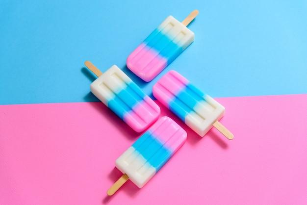 Frucht-eiscreme-stock, eis am stiel, eisknall oder gefrierfachknall mit copyspace auf blauem und rosa pastellhintergrund oder -beschaffenheit