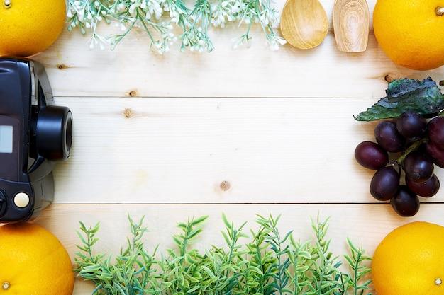 Frucht- und blumenrahmen mit kamera auf hölzernem hintergrund