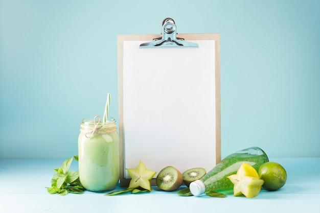 Frucht und smoothie mit leerem klemmbrett copyspace