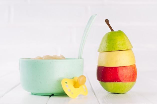 Fruchtapfel und birnenpüree in der schüssel nahe apfel auf weiß