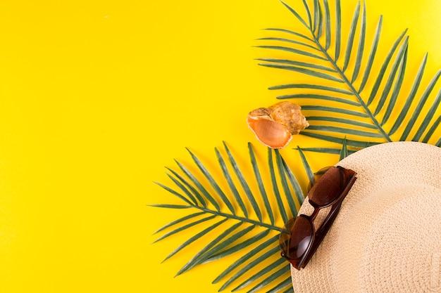 Fruchtbare tropische blätter nahe sonnenbrille mit hut und oberteil