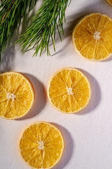 Fruchtbeschaffenheit mit getrockneter zitrone mit zweig des tannenbaums, draufsicht, weiße wand