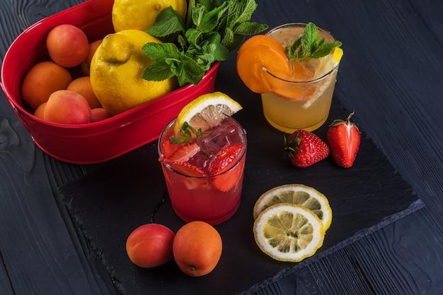 Fruchtcocktail mit frischen früchten und eis. in gläsern auf rustikalem schwarzem holzhintergrund