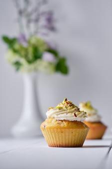 Fruchtcupcakes mit sahne, dekoriert mit gemahlener pistazie und blumen in einer vase auf einem weißen holztisch.