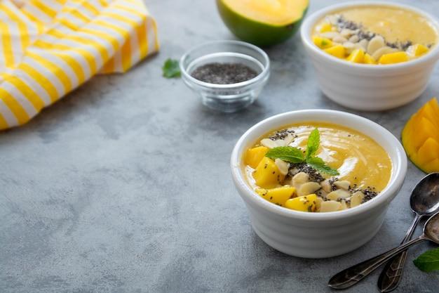 Fruchtgelbe smoothie-schale mit frischen mango-, bananen- und chiasamen. kopieren sie platz für text