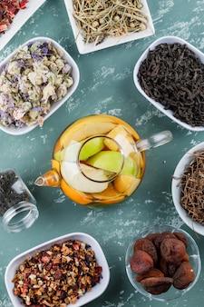 Fruchtgetränktes wasser in einer teekanne mit getrockneten aprikosen, kräutern, kirschstielen draufsicht auf einer gipsoberfläche