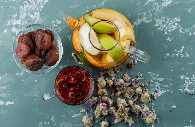 Fruchtgetränktes wasser in einer teekanne mit getrockneten aprikosen, kräutern, kräutertee draufsicht auf einer gipsoberfläche