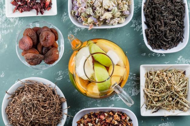 Fruchtgetränktes wasser in einer teekanne mit getrockneten aprikosen, kräutern und kirschstielen lag flach auf einer gipsoberfläche