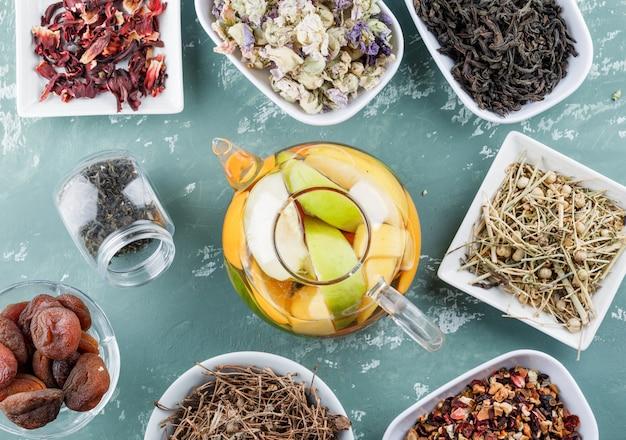 Fruchtgetränktes wasser mit getrockneten aprikosen, kräutern, kirschstielen in einer teekanne auf gipsoberfläche, draufsicht