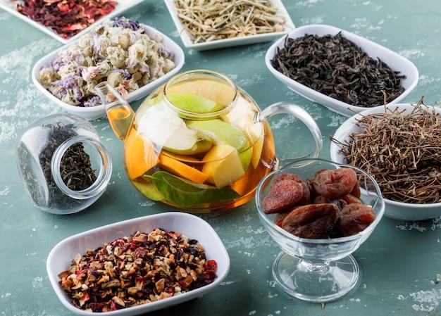 Fruchtgetränktes wasser mit getrockneten aprikosen, kräutern, kirschstielen in einer teekanne auf gipsoberfläche