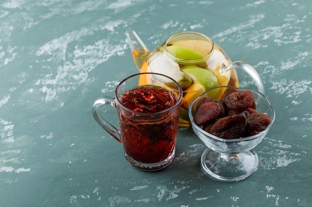 Fruchtgetränktes wasser mit getrockneten aprikosen, kräutertee in einer teekanne auf gipsoberfläche
