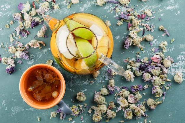 Fruchtgetränktes wasser mit getrockneten blumen, kräutertee in einer teekanne auf gipsoberfläche, draufsicht
