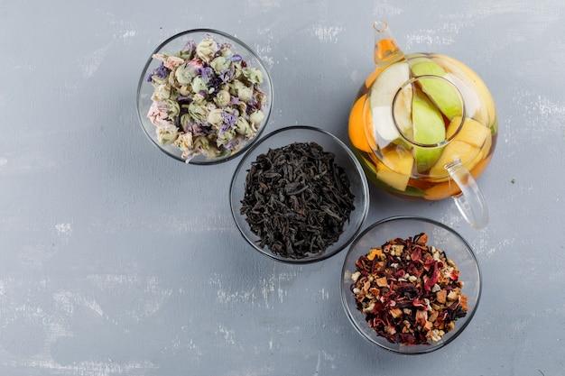 Fruchtgetränktes wasser mit getrockneten kräutern in einer teekanne auf gipsoberfläche, draufsicht