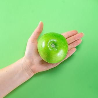 Fruchtgrüner apfel ingwer auf farbigem hintergrund hände saft lecker