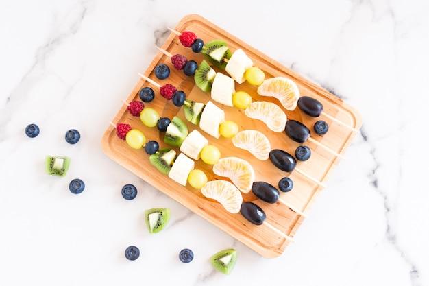 Fruchthäppchen auf einem holzbrett. leckeres und gesundes essen. mischung aus mandarine, kiwi, banane, trauben. ansicht von oben.