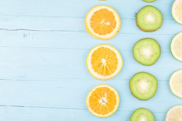 Fruchthintergrund. buntes frisches obst auf blauem holzbrett.
