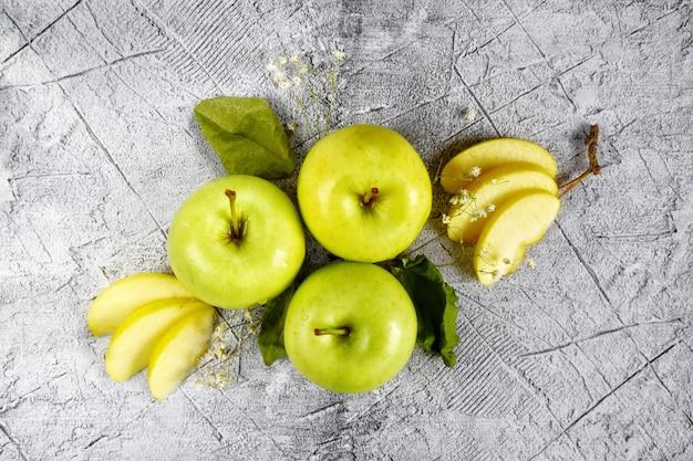 Fruchtige fantasie drei ganze grüne äpfel und apfelschnitze. nahansicht. veganes essen, gesunder lebensstil.