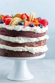 Fruchtiger kuchen mit frischen früchten und sahne auf stander