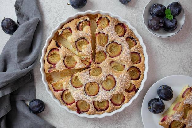 Fruchtiger, süßer kuchen mit frischen pflaumen. in einer weißen auflaufform mit puderzucker.