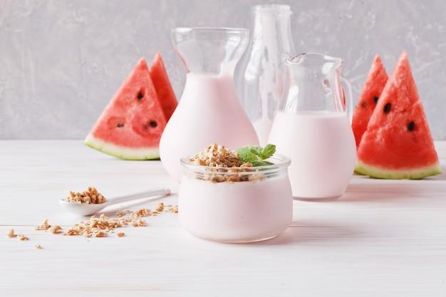Fruchtjoghurt, smoothies in einem glaskrug, müsli und geschnittene wassermelone