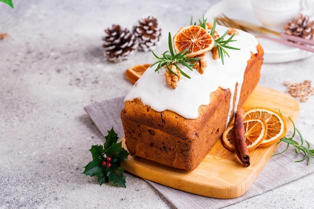Fruchtkuchen bestäubt mit zuckerglasur, nüssen und trockener orange auf stein. weihnachts- und winterferien hausgemachten kuchen
