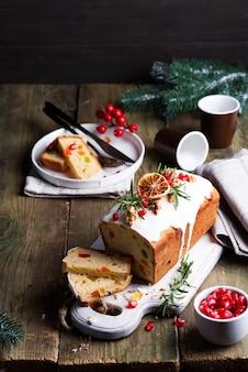 Fruchtkuchen wischte geschnitten mit zuckerglasur, nüssen, kerngranatapfel und trockener orange nahaufnahme ab. weihnachts- und winterferien hausgemachten kuchen
