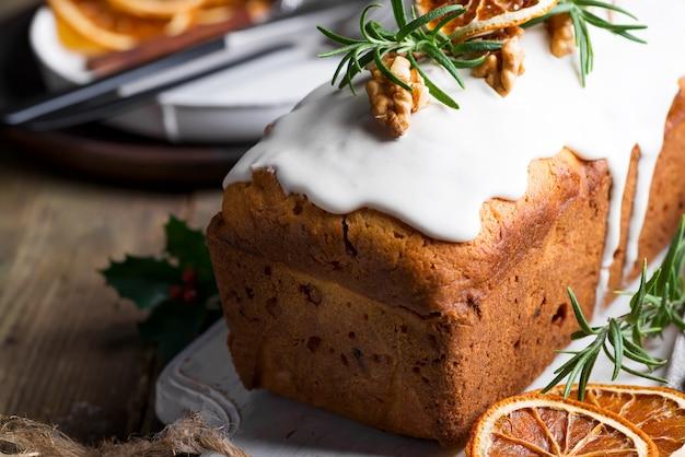 Fruchtkuchen wischte mit zuckerglasur, nüssen und trockener orange nahaufnahme ab. weihnachts- und winterferien hausgemachten kuchen