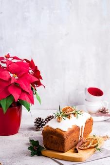 Fruchtlaibkuchen bestäubt mit zuckerglasur, nüssen und trockenem orange stein. weihnachts- und winterferien weihnachtsstern auf