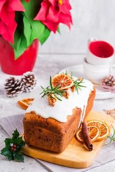 Fruchtlaibkuchen wischte mit zuckerglasur, nüssen und trockener orange auf stein ab. weihnachts- und winterferien hausgemachten kuchen